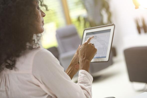Woman using tablet to operate smart home technology