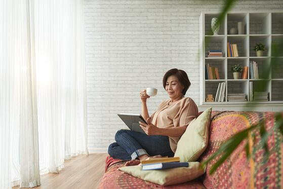 Woman relaxing in living room with books and a cup of coffee
