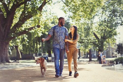 Couple walking their dog through city